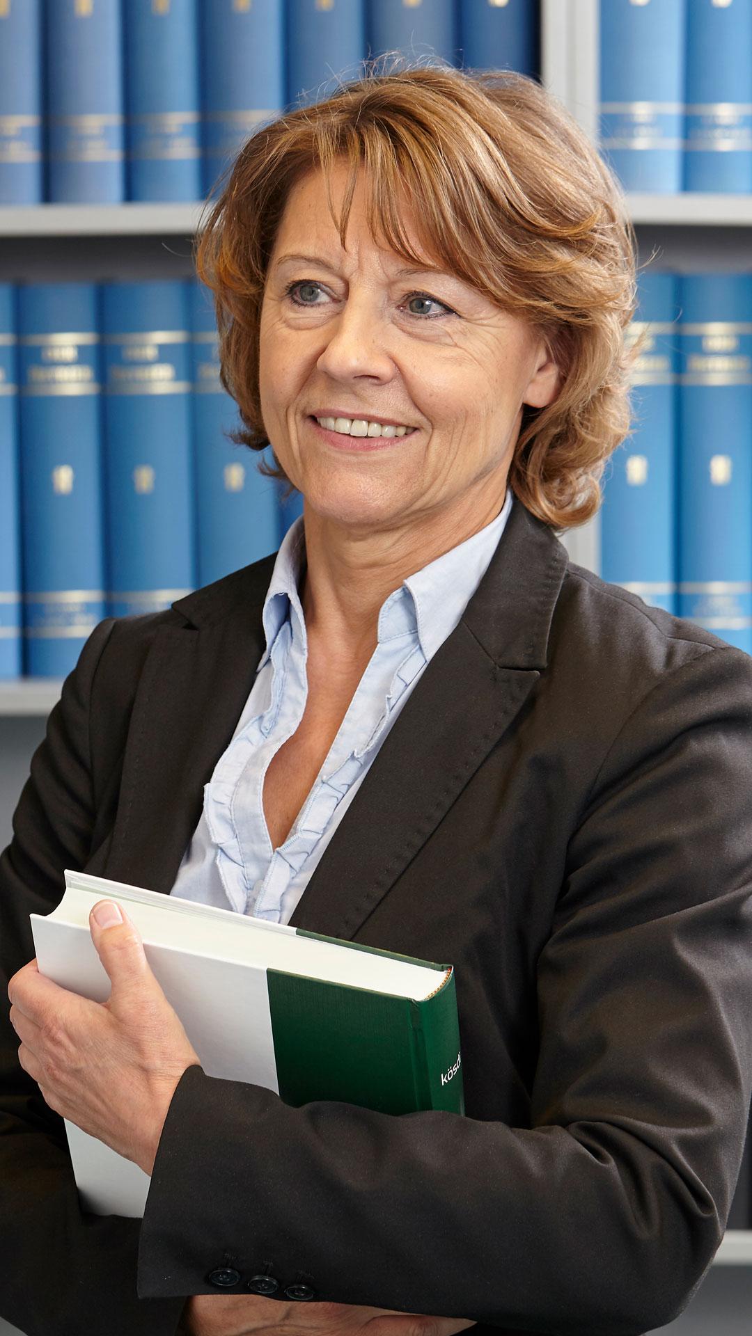 Steuerberaterin Brigitte Müller steht vor einem Schrank mit Büchern